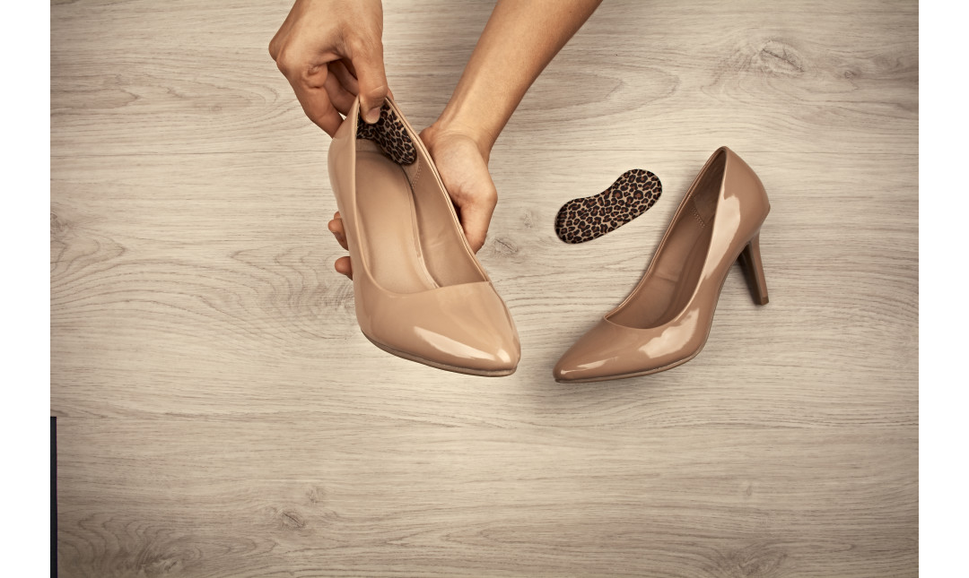 hands pressing leopard print foam heel liner into back of a pair of nude pumps
