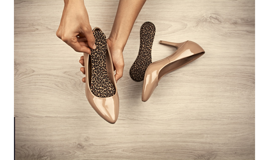 hands inserting leopard print foam insoles into a pair of nude pumps
