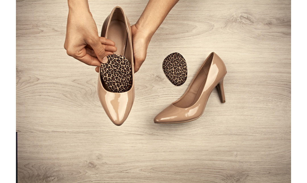 hands placing leopard ball of foot cushions into a pair of tan high heels