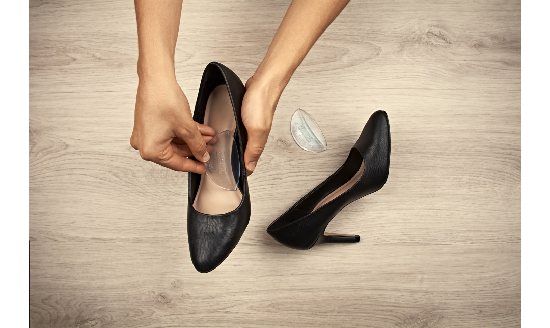 hands placing clear gel arch supports into a pair of black high heels