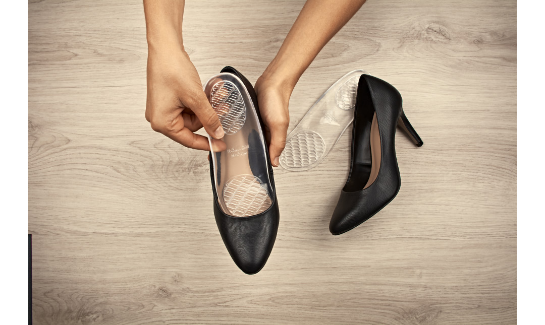 hands placing clear gel insole with arch support into a pair black high heels