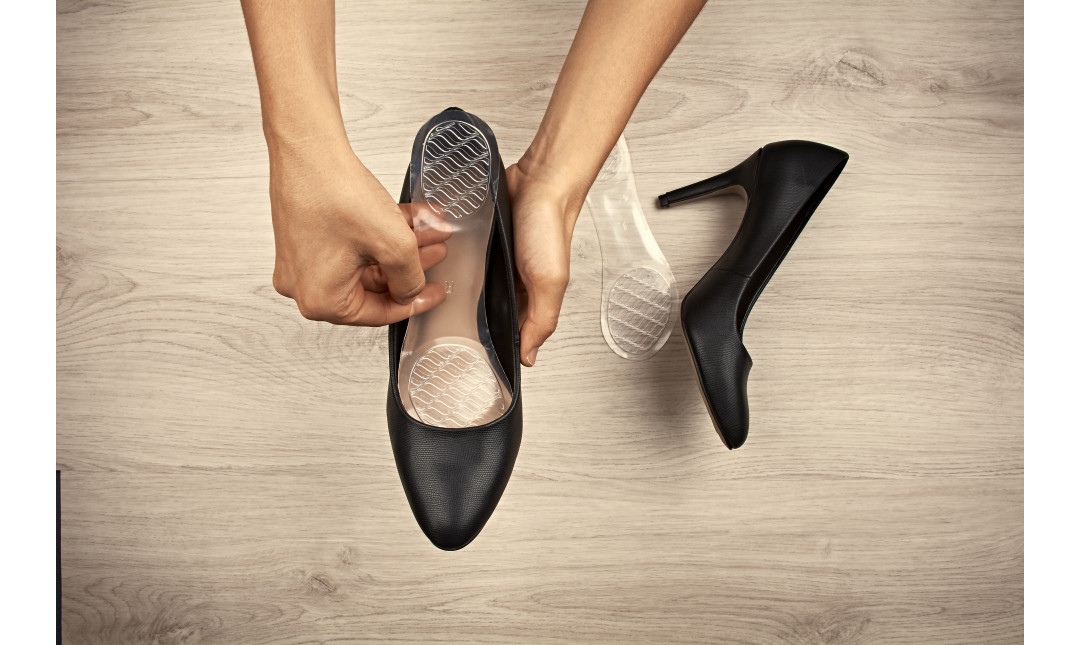 hands placing clear gel insole into black high heels