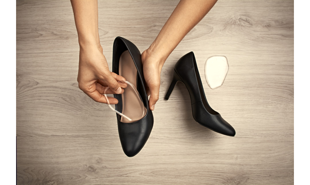 hands placing gel forefoot cushion into heels of black shoes