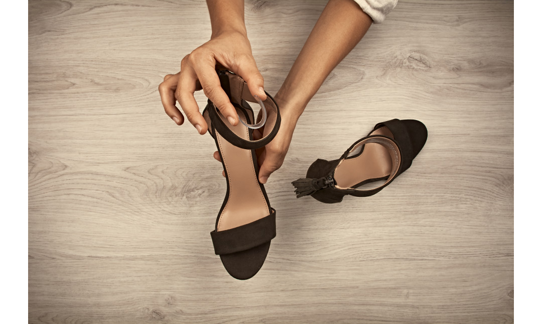 hands placing gel strap liners into high heel sandals