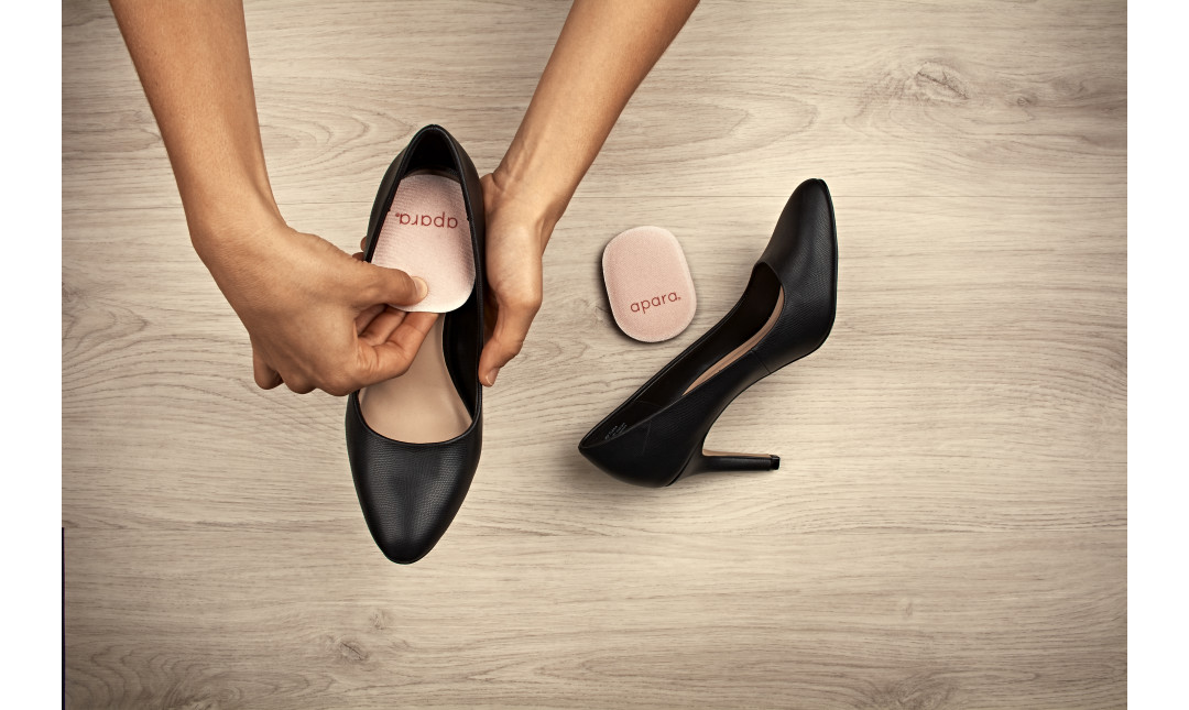 hand placing a memory foam heel cushion onto insole of black stilletos