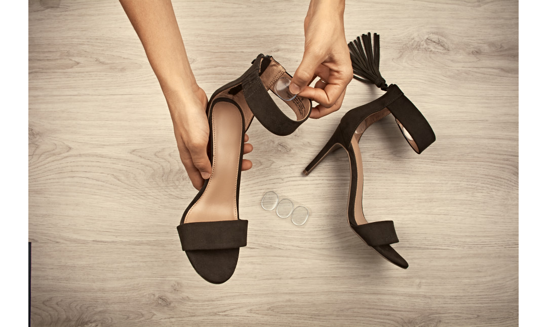 hands inserting gel adhesives into high heel sandals